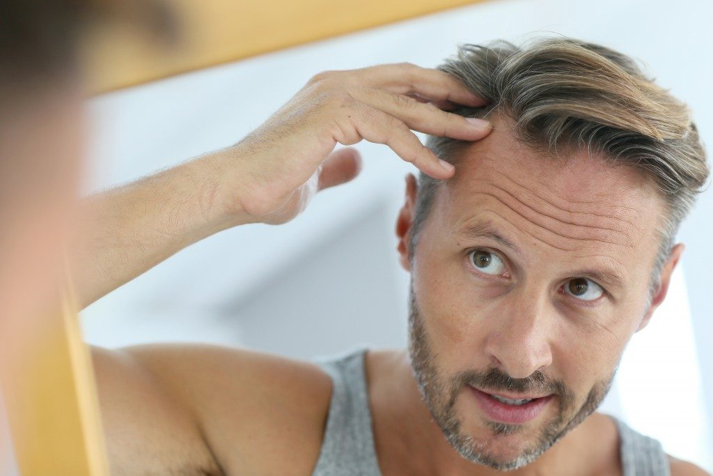 Man looking at his hair in front of a mirror