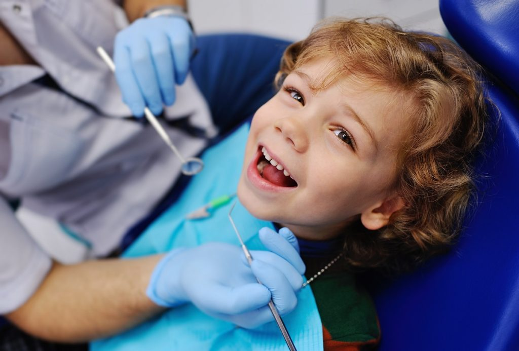 Kid smiling on dentist chair