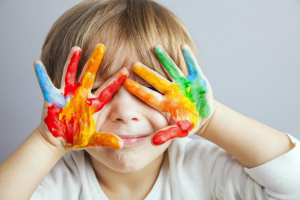 Boy whose hands are covered with paint