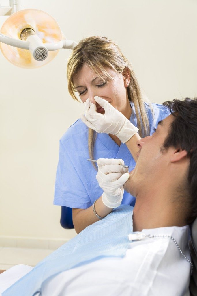 dentist holding her nose and patient with open mouth