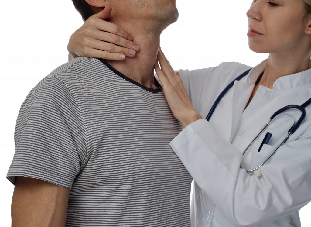 Man having his Thyroid being checked by a doctor