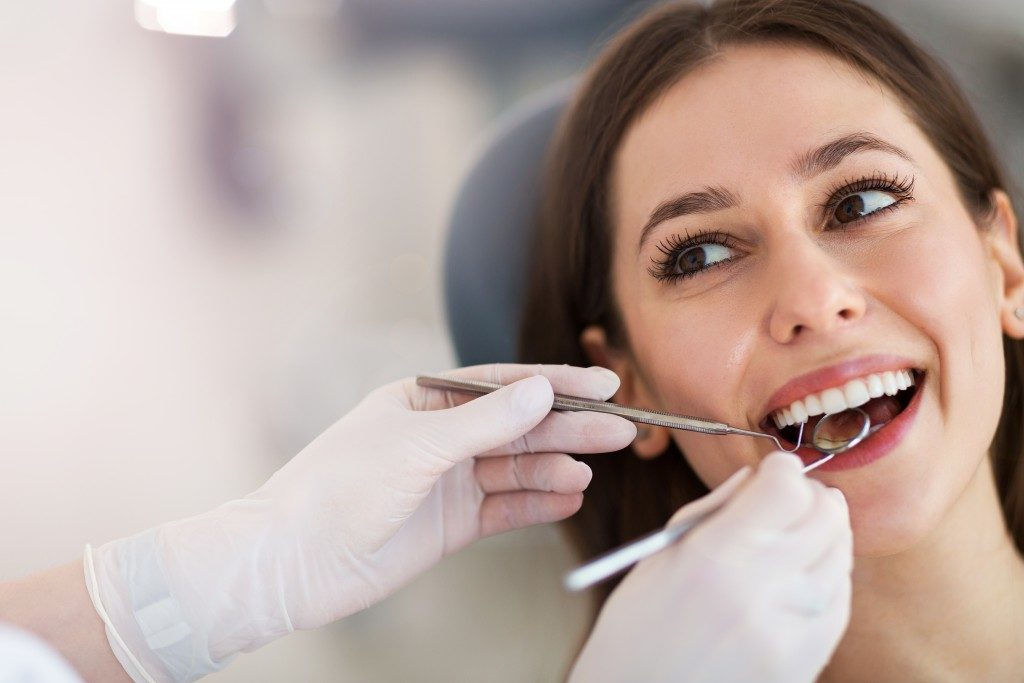 woman getting her teeth check by a dentist
