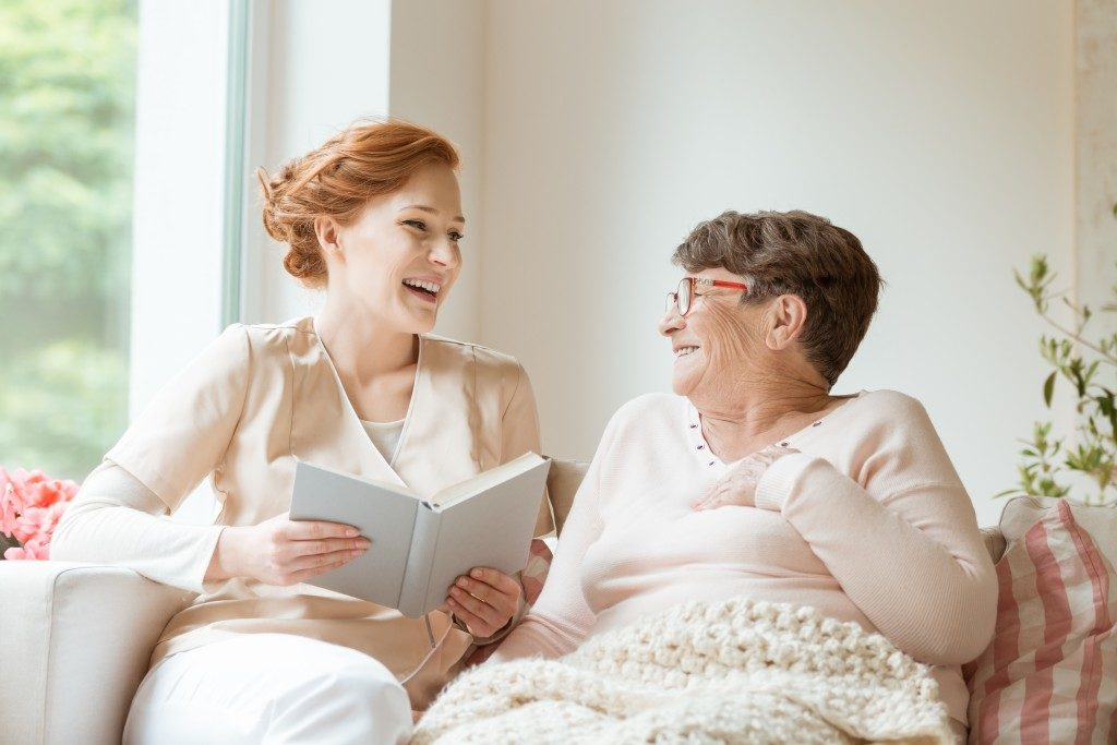 Elder woman being read to by caretaker