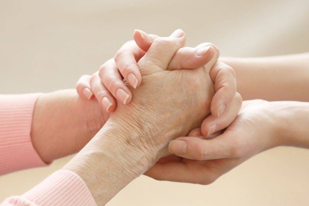 Woman holding elderly woman's hands