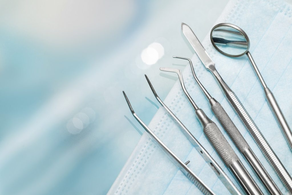 small surgical equipments laying on top of blue mask