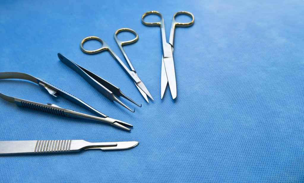 small surgical equipments on top of a blue cloth