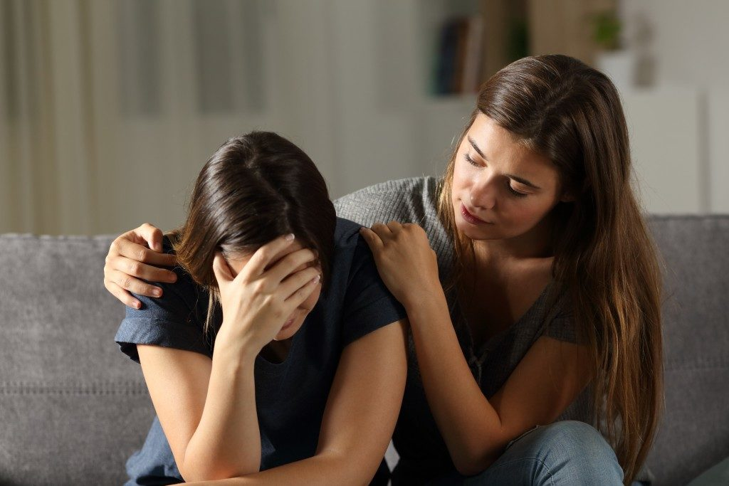 woman crying in grief while her friend comforts her