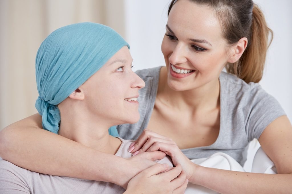 Woman with cancer being embraced