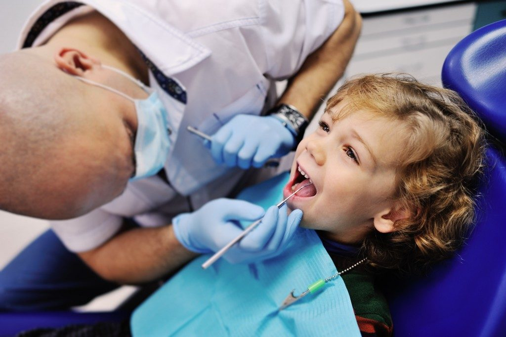 Dentist examines teeth of little boy
