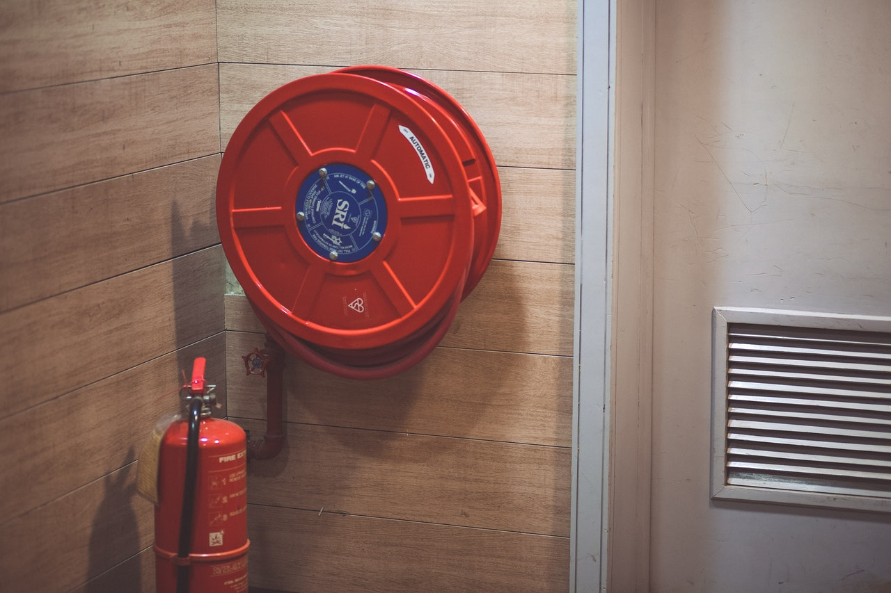 fire extinguisher next to a hose reel
